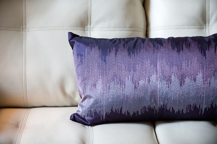 cream-leather-sofa-purple-pillow