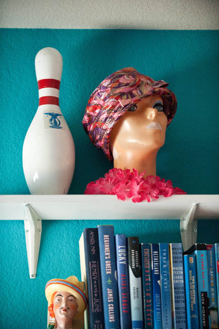 A vintage bowling pin and mannequin head hang out in a teal blue office on white shelves.