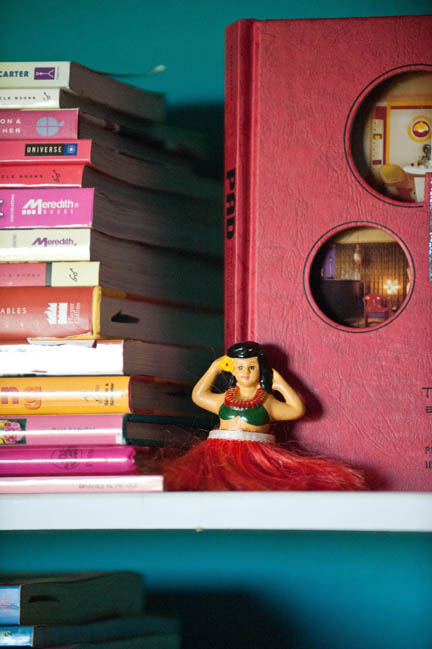 A hula girl perched on a shelf in a home office.