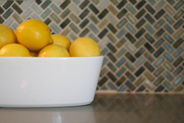 lemons against modern herringbone kitchen backsplash