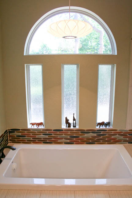 Mid century modern master bathroom remodel in Austin, TX featuring glass mosaic tile in earth tones.