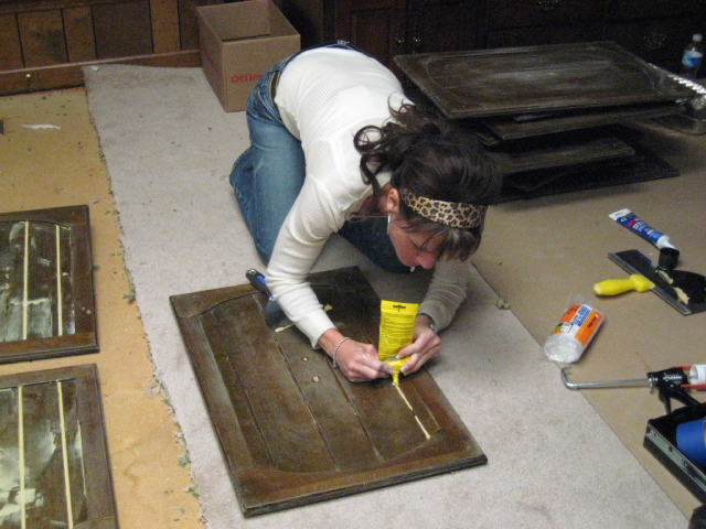 Trish Beaudet fills dated paneling with wood putty, in preparation for repainting the cabinetry during Season 3's kitchen challenge.