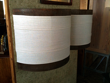 Sconces made from reclaimed mesh cylinder cut in half and wrapped with linen.
