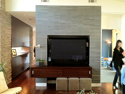 Between the dark black box and the tile treatment, this TV niche looks like a fireplace at first glance.