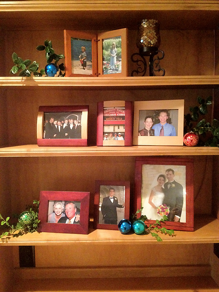 AFTER: Family photos in wood frames are grouped in one bookcase in Natasha's Rollingwood living room in Austin, TX.