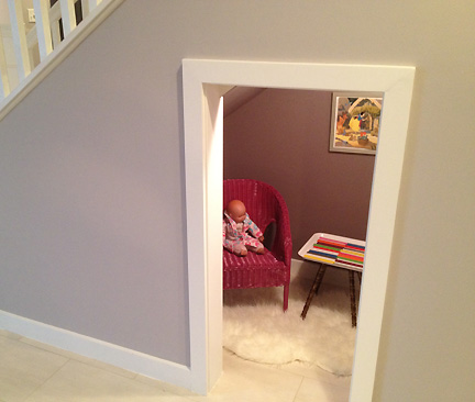 A child's getaway is created in a nook under the stairs with mod furniture and a flokati rug.
