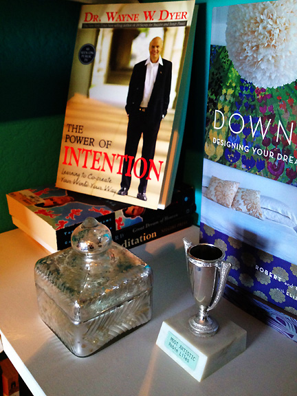 "My ""helpful people"" corner includes the Wayne Dyer book, The Power of Intention, a small silver trophy won in high school for ""Most Artistic"" and a silver-toned mercury glass box from Anthropologie holding a list of people I hope will help me."