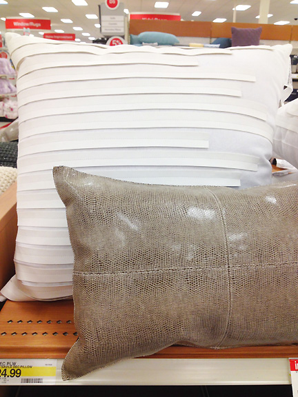 A monochromatic white pillow and a snakeskin lumbar pillow by Nate Berkus at Target.
