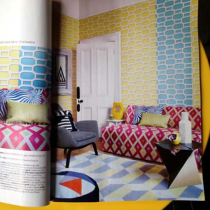 A pink geometric patterned sofa and blue and yellow geometric wallpaper, as featured in Livingetc's February 2013 issue of the UK modern home decor magazine.