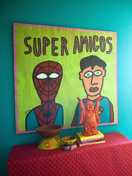 Super Amigos, by Paco, hangs above a hot pink fabric covered filing cabinet styled like a credenza in the teal office of Room Fu Design Guru, Robin Callan.