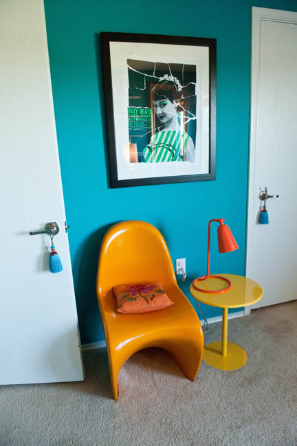 An orange S chair and round yellow side table sit beneath silkscreened concert poster in the home office of Robin Callan, design guru for Room Fu in Austin, TX.