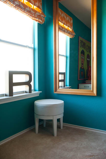 A full length mirror hung next to a corner window creates the illusion of more windows in a cramped office in Austin, TX.