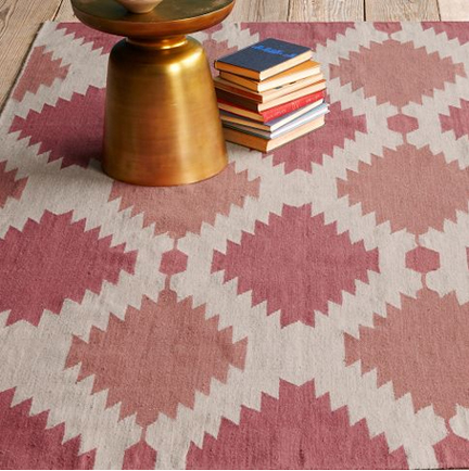 West Elm wool dhurrie rug in modern shades of rose, pink, and soft red in a geometric pattern.