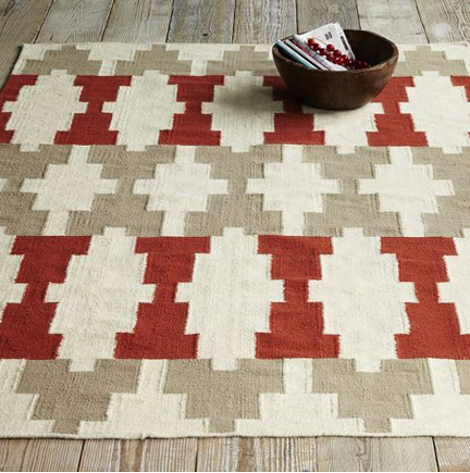 West Elm dhurrie wool modern geometric rug in shades of rust red, gray and white.
