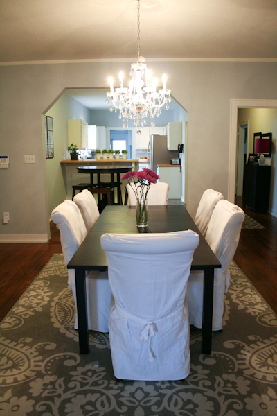 sm_white dining room slipcovered chairs crystal chandelier gray walls 2