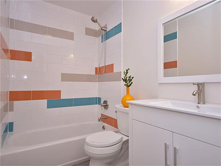 Modern kids' bathroom featuring elongated subway tiles in teal blue, tangerine orange, gray and white, with a white lacquer bathroom vanity and porcelain sink/countertop.