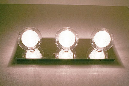 Contemporary 3-light bathroom vanity fixture, featuring clear round globes and rectangular mounting base.