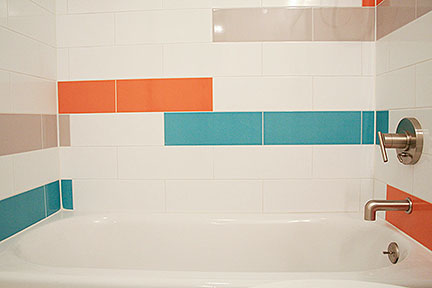 Modern tub surround tile design featuring teal, orange, white, and gray elongated subway tiles.