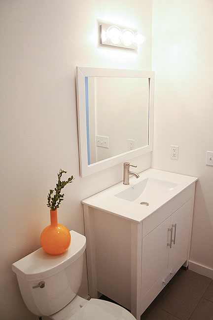 White lacquer bathroom vanity cabinet with porcelain countertop and integrated sink. White framed mirror, contemporary bathroom vanity light fixture.
