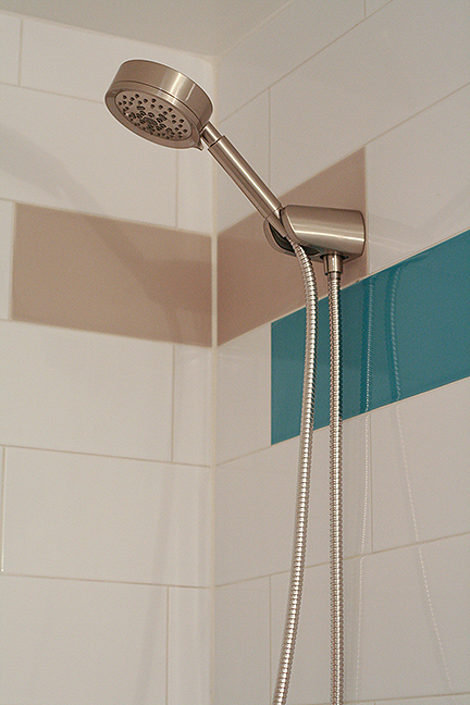 Modern handheld showerhead in brushed nickel, surrounded by elongated subway tiles in teal blue, white, and gray.
