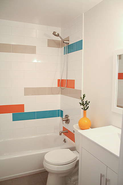 Modern kid's bathroom tub & shower surround design, featuring teal, bright orange, gray and white elongated subway tiles.