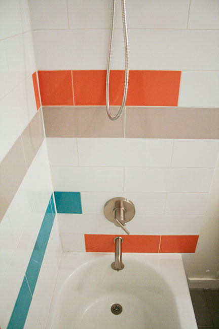 Modern tub surround in hall bathroom, featuring elongated subway tiles in teal blue, tangerine orange, gray and white elongated subway tile.