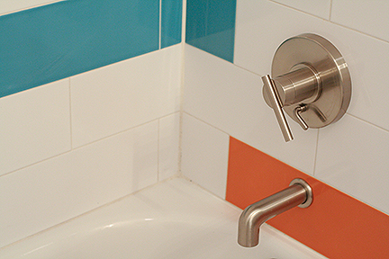 Contemporary tub spout and tub/shower controls in brushed nickel, surrounded by modern, elongated subway tiles in teal blue, bright orange, and white.