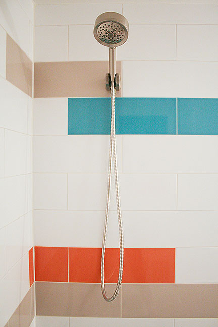 Modern bathroom tile design featuring elongated subway tiles in teal blue, bright orange, taupe-gray, and white, with simple brushed nickel plumbing fixtures.