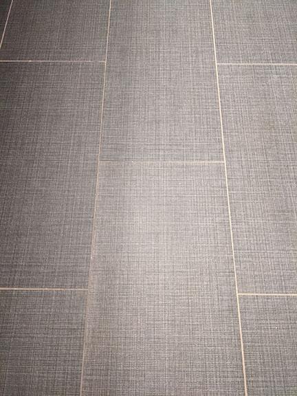 Fabric textured gray floor tile closeup photo in Austin modern bathroom remodel.