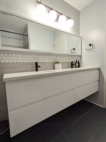 Floating white lacquer double vanity in modern gray bathroom remodel in Austin featuring large white penny accent tile, quartz countertops, and black plumbing fixtures.