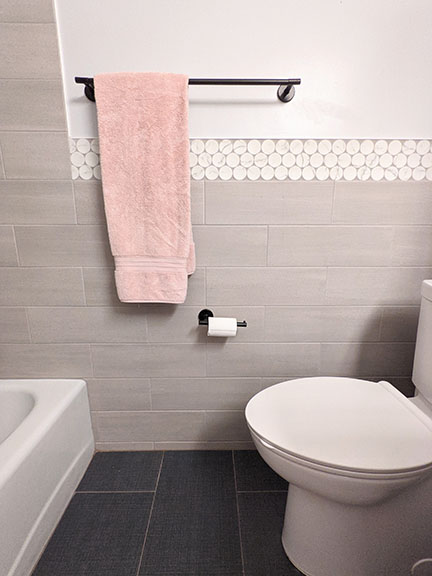 Blush peach bath towel in modern gray bathroom remodel featuring large white and gray penny round accent tile.