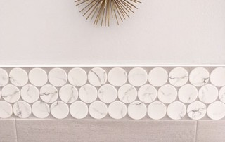 Brass mid-century modern starburst wall art in bathroom remodel featuring large white penny round accent tile in Austin, Tx.