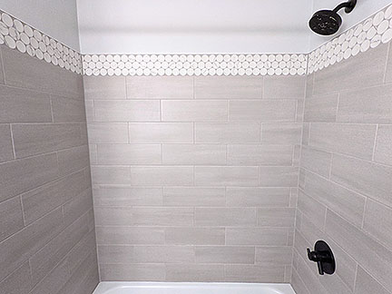 Gray tub and shower surround in Austin TX featuring large white and gray marble penny round accent tile, light gray field tile, and dark charcoal gray floor with black plumbing fixtures in modern bathroom remodel.