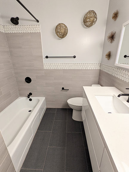 Gray tub and shower surround in Austin TX featuring large white and gray marble penny round accent tile, light gray field tile, and dark charcoal gray floor with black plumbing fixtures and natural twig and brass accessories in modern bathroom remodel.