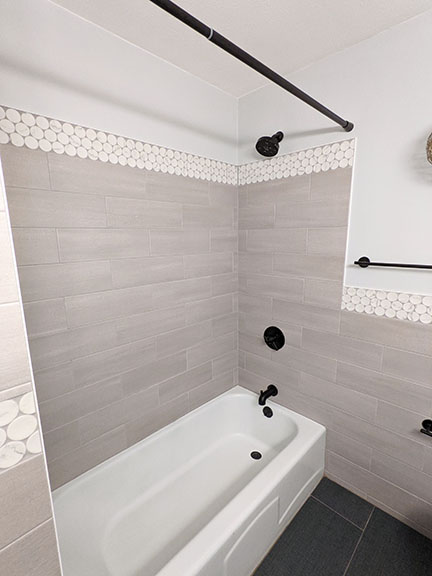 Gray tub and shower surround in Austin TX featuring large white and gray marble penny round accent tile, light gray field tile, and dark charcoal gray floor in modern bathroom remodel.